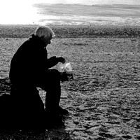Eating fish and chips on snettisham beach.black & white
